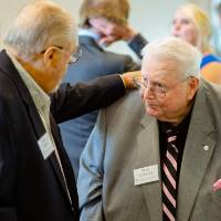 Seymour Padnos putting his hand on a guest's shoulder at the Foundation Annual Meeting